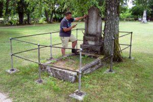Pekka Linnainen tutkimassa Wirin muistomerkin tekstiä Kihelkonnan hautausmaalla 27.7.2011